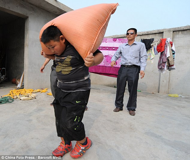 What a weightlifter! Here the little boys lifts a 40kg bag of wheat