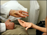 Dr. Lauro Halstead examines the hand of patient with polio