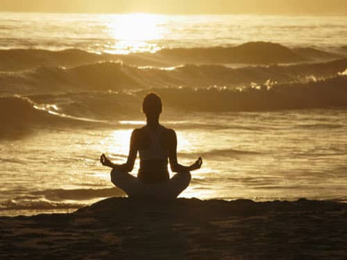 Silhouette of woman meditating on beach