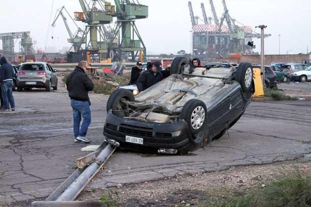 Homens observam carro capotado por fenômeno em Taranto nesta quarta-feira (28) (Foto: AP)