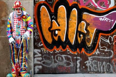 Un hombre vestido de payaso pide limosna en la calle.| Domenec Umbert