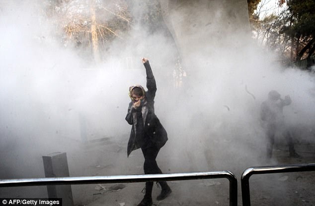 An Iranian woman escapes tear gas during the unrest at the University of Tehran as students joined in the country's ongoing protests