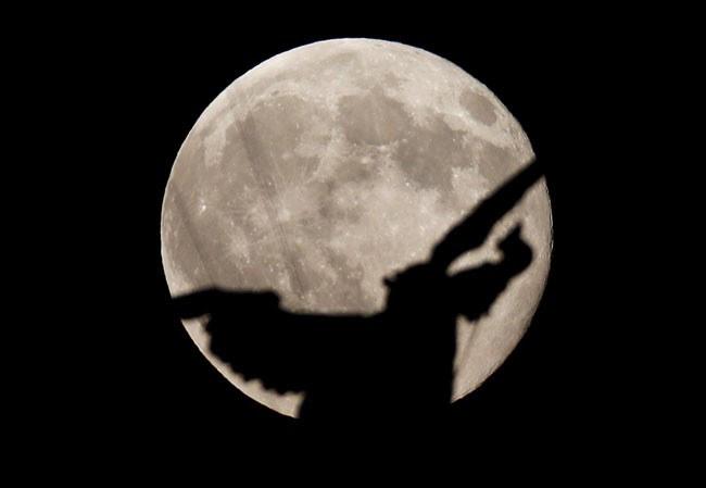 A 'lua azul' na noite desta sexta-feira (31), atrás do anjo que fica sobre o Castelo de Santo Ângelo em Roma (Foto: Max Rossi/Reuters)