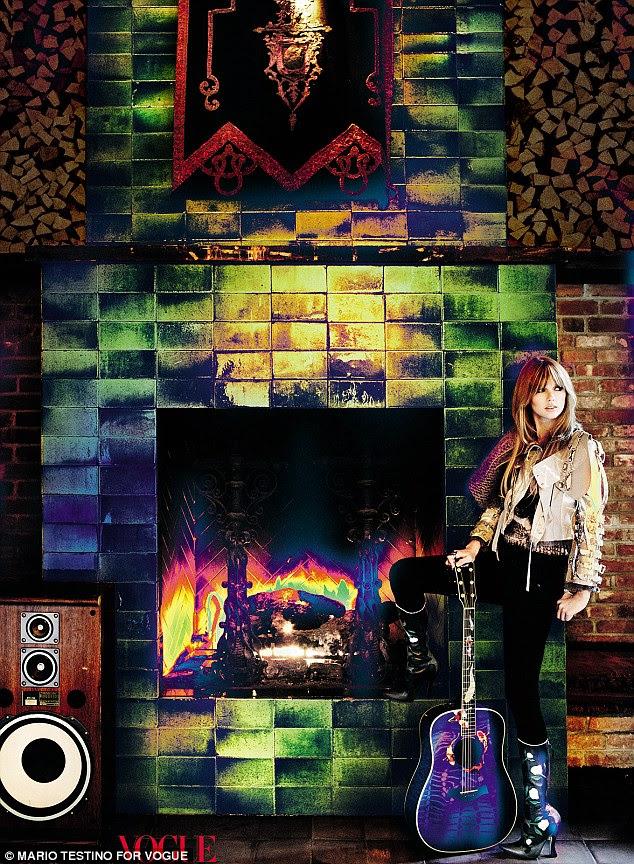 País em cor: Taylor usar um par de calças pretas justas e uma jaqueta creme decorado com botas de salto alto que ela posa por uma lareira com uma guitarra em um tiro