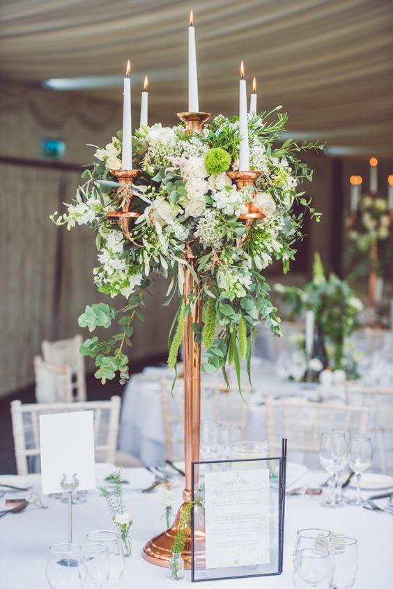 einen hohen Kupfer-Kerze-stand mit üppigem grün und neutral Blumen als eine atemberaubende Herzstück