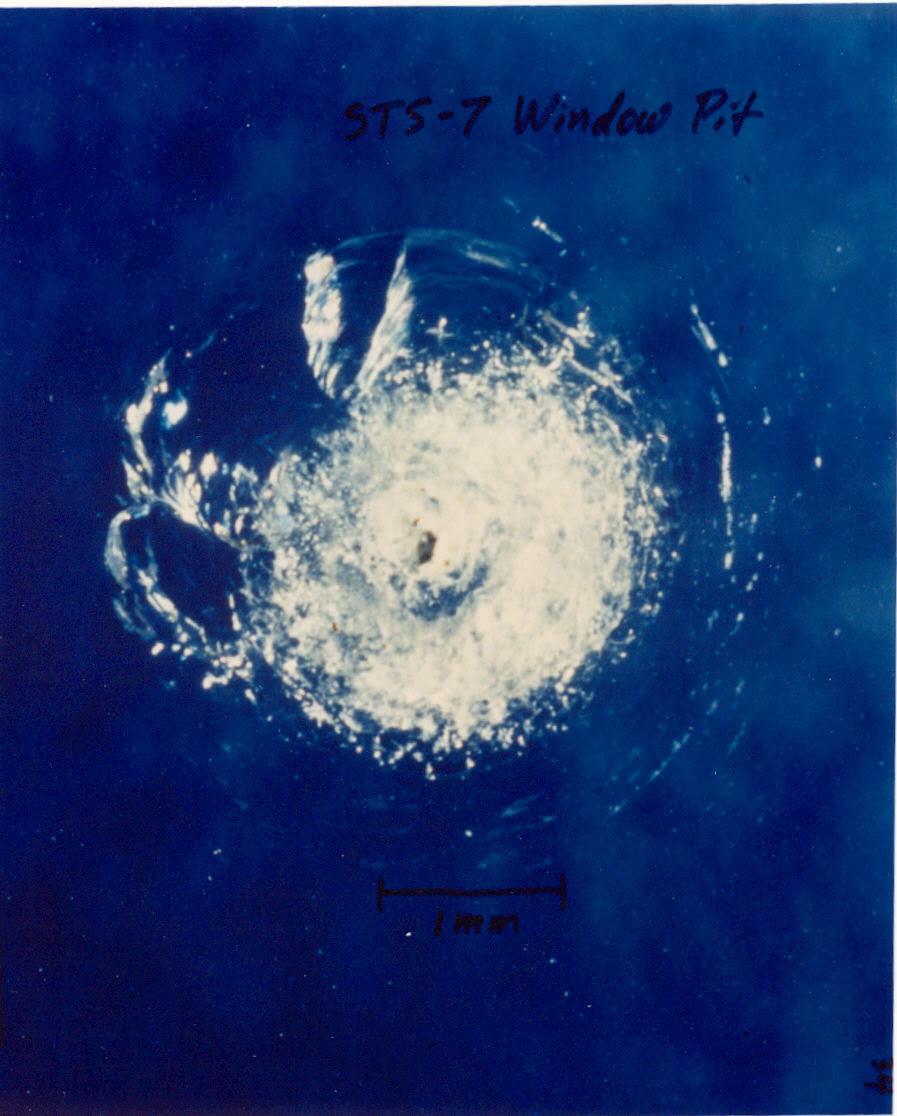 Um pingo de tinta deixou este rombo na superfície da janela frontal do Ônibus Espacial Challenger, na STS-7. Imagem de Wikipedia.org.