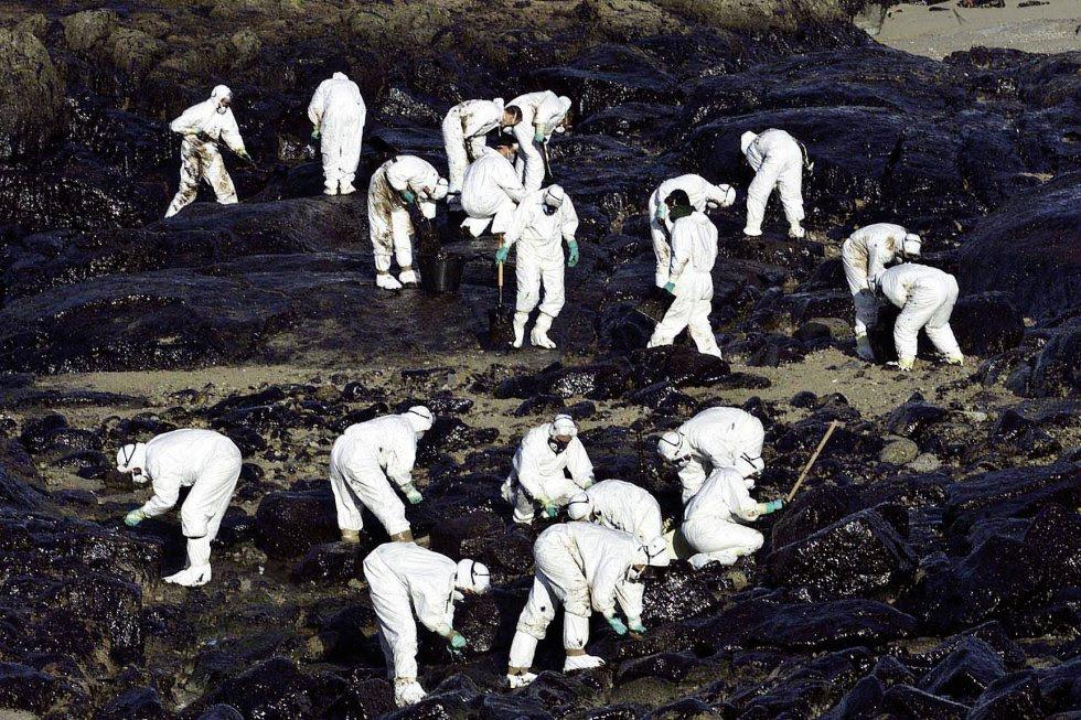Voluntarios recogen chapapote en la Costa da Morte (Galicia) el 6 de diciembre de 2002. El naufragio del petrolero Prestige causó uno de los mayores desastres naturales en la historia de España. La marea negra afectó a 2.000 kilómetros de costa y movilizó a miles de voluntarios.