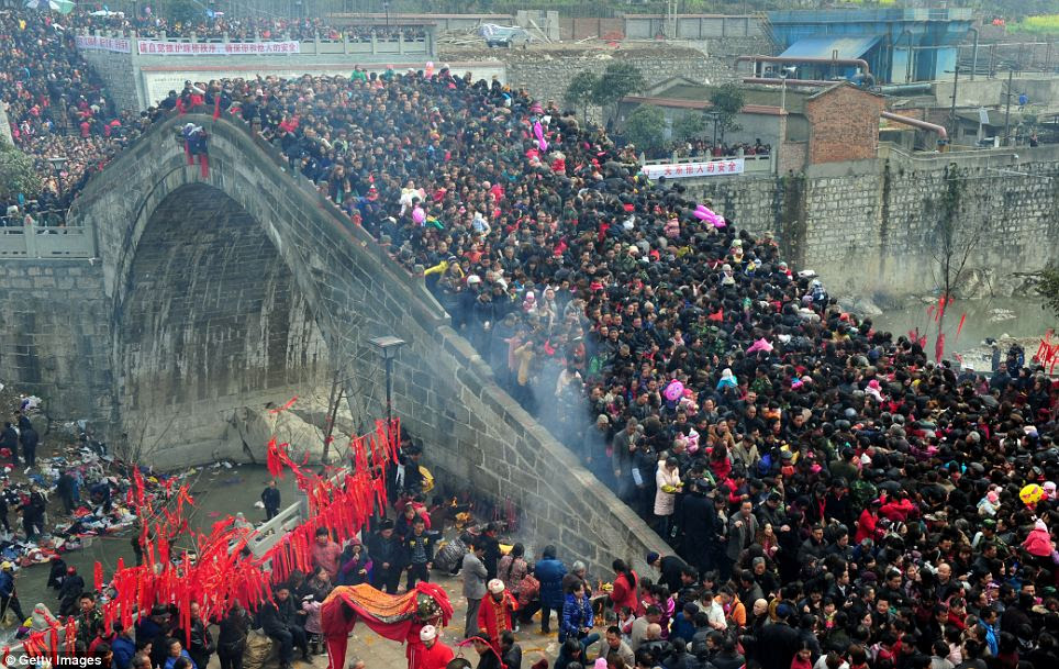 Health and happiness: Local residents in China's Sichuan Province gather at the Taiping Bridge for the Spring Sacrificial Rites festival to pray for good luck