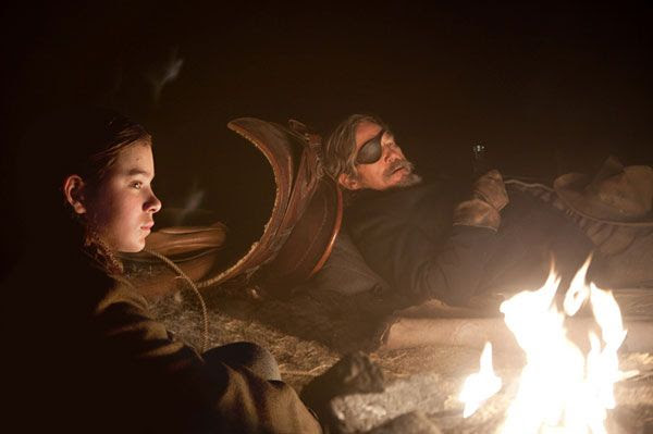 Mattie Ross (Hailee Steinfeld) and Rooster Cogburn (Jeff Bridges) take a rest during their trip to find and capture the man who killed Ross' father in TRUE GRIT.