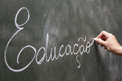 Foto mostra um quadro negro e uma mão escrevendo a giz branco a palavra educação