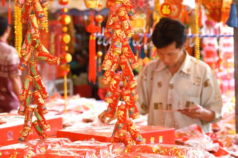 Close up of a colourful street stall with hanging firecrackers