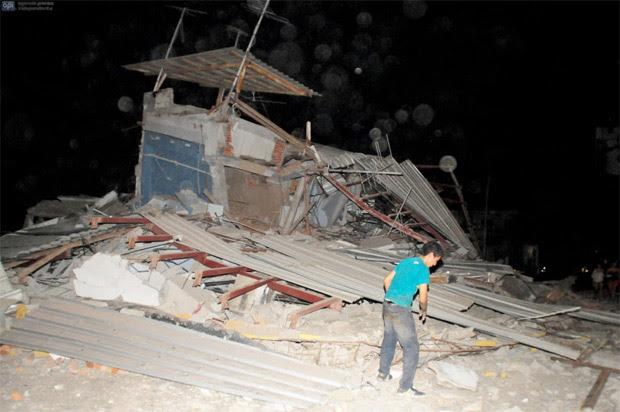 Homem diante de prédio destruído em Guaiaquil após forte terremoto atingir o Equador