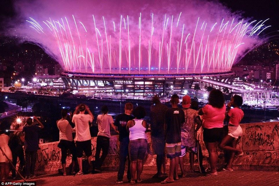 As pessoas assistem fogos de artifício explodem sobre o estádio do Maracanã, a partir da favela da Mangueira, durante a cerimônia de abertura dos Jogos Olímpicos Rio 2016 abertura
