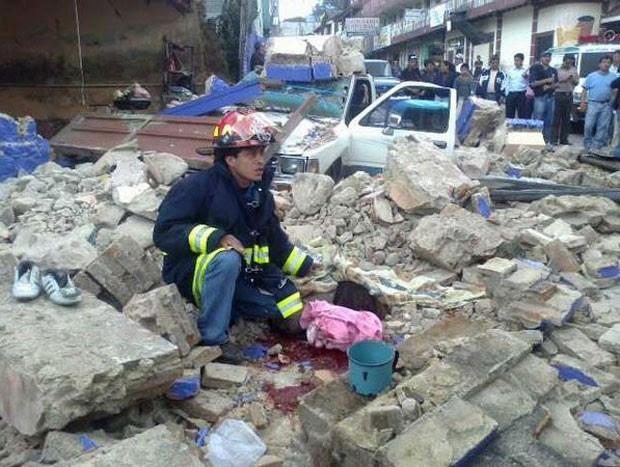 Bombeiro em meio a desabamento provocado pelo terremoto desta quarta-feira (7) em San Marcos, na Guatemala (Foto: AFP)