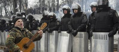 Un manifestante suona la chitarra di fronte ai poliziotti a Kiev (Reuters)