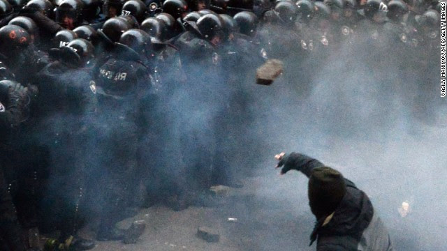 A Ukrainian protester throws stones at riot police during the clashes outside the president's office on December 1.