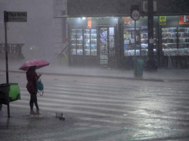Pedestre enfrenta temporal na Praça Ramos, no centro de São Paulo, na tarde desta segunda-feira (16) (Foto: Cris Faga/Fox Press Photo/Estadão Conteúdo)