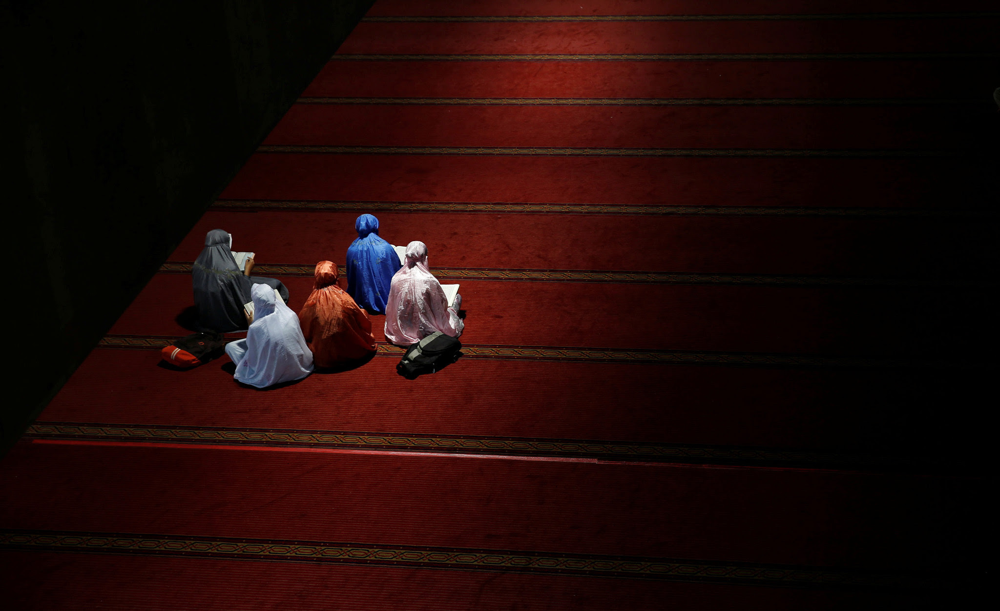 A group of youths read Koran as they wait to break the fast during the holy month of Ramadan inside Istiqlal mosque in Jakarta, Indonesia June 9, 2016.