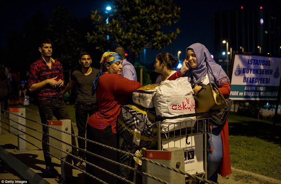 passageiros evacuados estão com carrinhos lotados de bagagem fora do aeroporto depois de fugir para salvar suas vidas