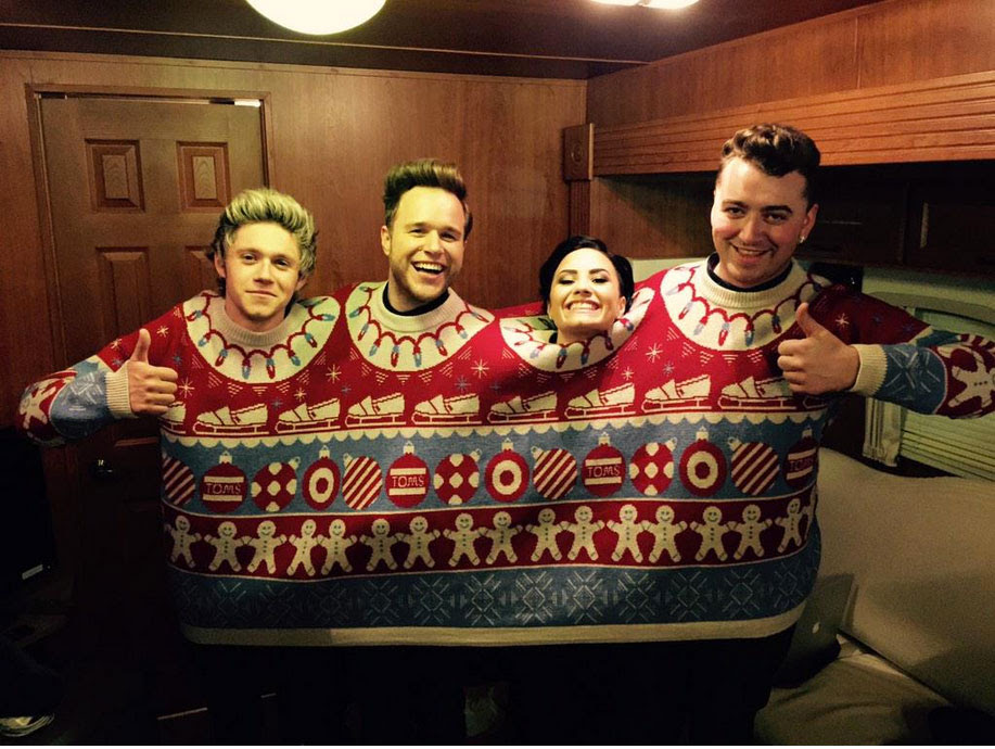 Demi Lovato got in the Christmas spirit by snuggling up with three hotties in this amazing four-person ugly Christmas sweater!