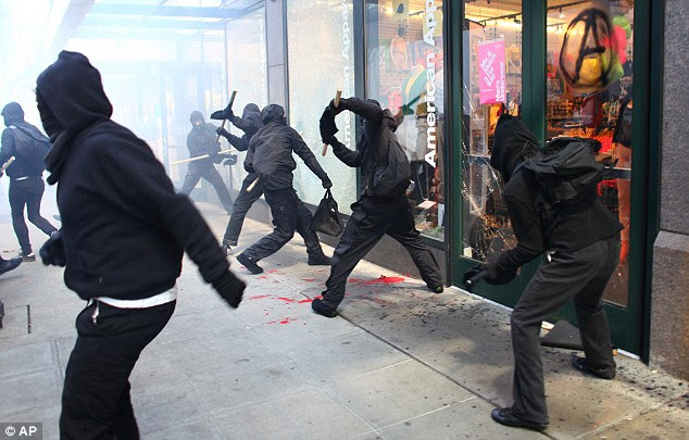 Gang: About two dozen of the hundreds of protesters that participated in the march shattered windows and caused mayhem in Seattle