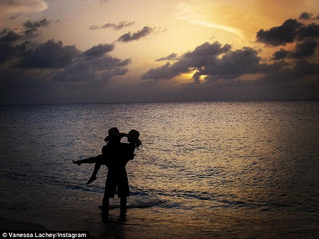 So in love: In honour of their five year wedding anniversary on Friday, Vanessa Lachey shared a romantic photo of husband Nick Lachey cradling her in his arms at sunset