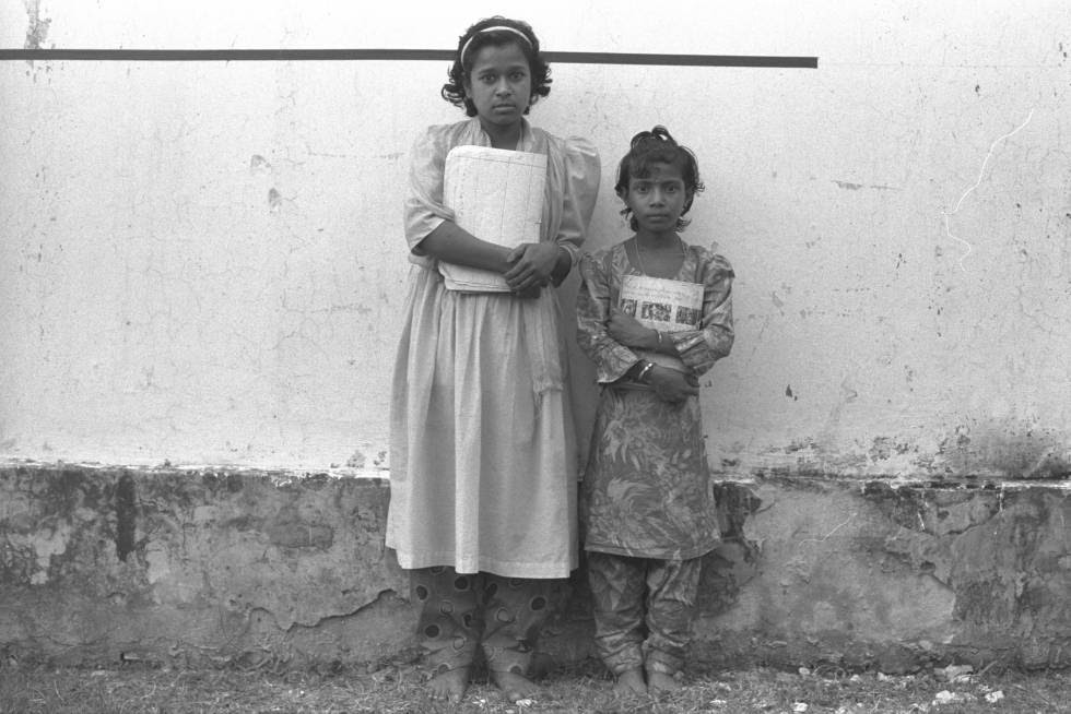 La altura media cayó 12 centímetros en Bangladesh entre 1937 y 1992. Estas niñas, fotografiadas en 1997, son Juhora y Asma Akter, primas nacidas en el mismo año en una zona rural cerca de Shahrasti. Asma es considerablemente más baja que su prima y está bastante por debajo de lo que debería medir según la Organización Mundial de la Salud (marcado por la línea negra en la pared) debido, dice Unicef, a que sufrió desnutrición crónica en su primera infancia. Bangladesh es , pese a los avances, el séptimo ´páis del mundo con mayor número de niños en esta situación.