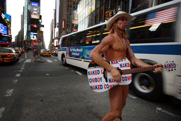The street performer Robert Burck, who is known as the Naked Cowboy, performs for pedestrians June 24, 2008 in Times Square in New York City. The $6-million lawsuit filed by the Burck against M&Ms candy maker Mars Incorporated can go forward on grounds of trademark infringement a New York judge has ruled. Burck filed the suit about video billboards depicting a blue M&M dressed in his signature outfit in an animated cartoon it ran on two video billboards in Times Square.
