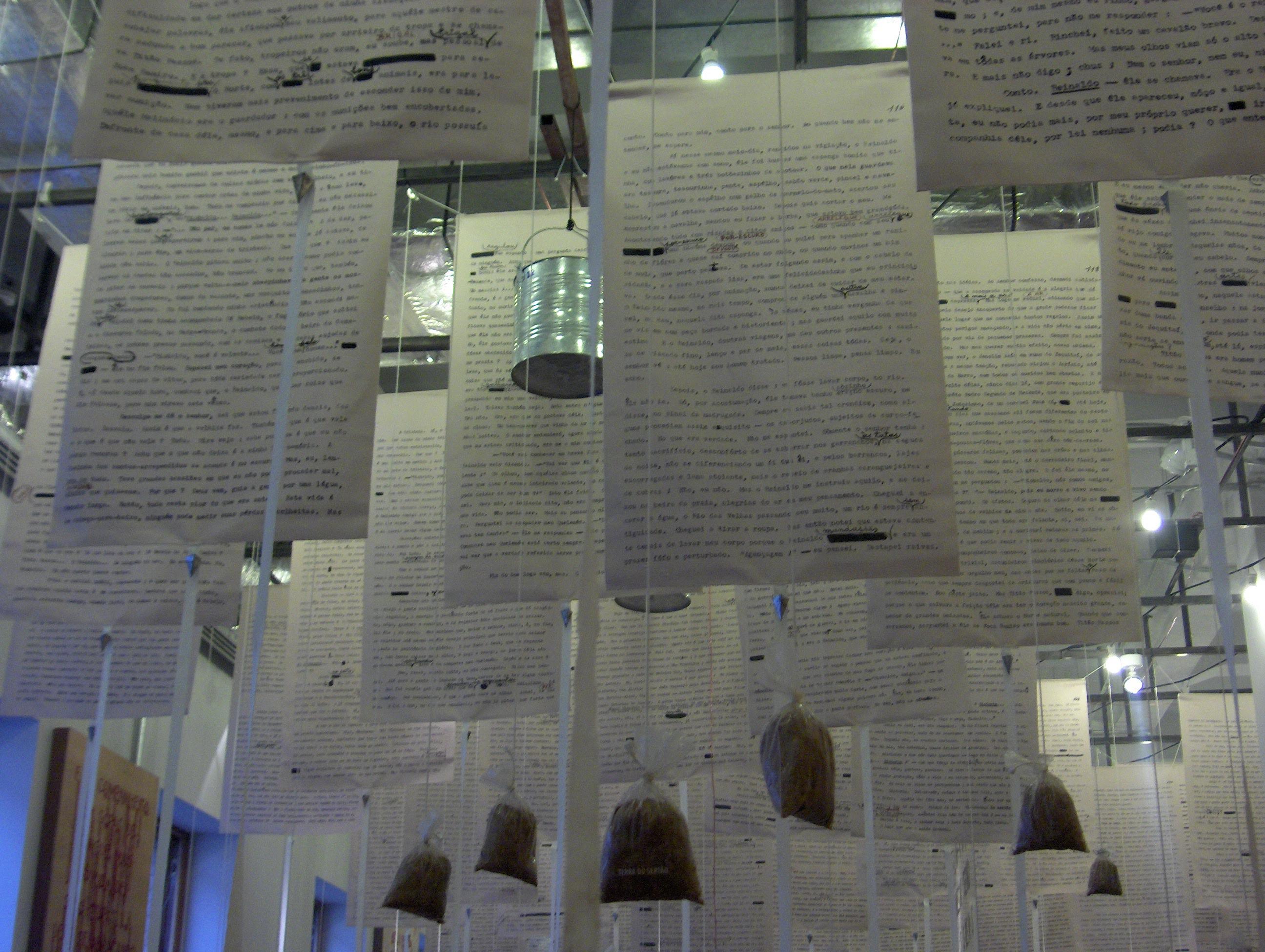 """Fotografia do interior do Museu da Língua Portuguesa, com vários """"banners"""" pendentes do teto, com com textos escritos."""
