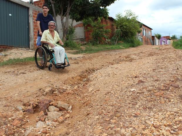 Em rua cheia de buracos, o cadeirante precisa da ajuda dos netos para sair de casa (Foto: Patrícia Andrade/G1)