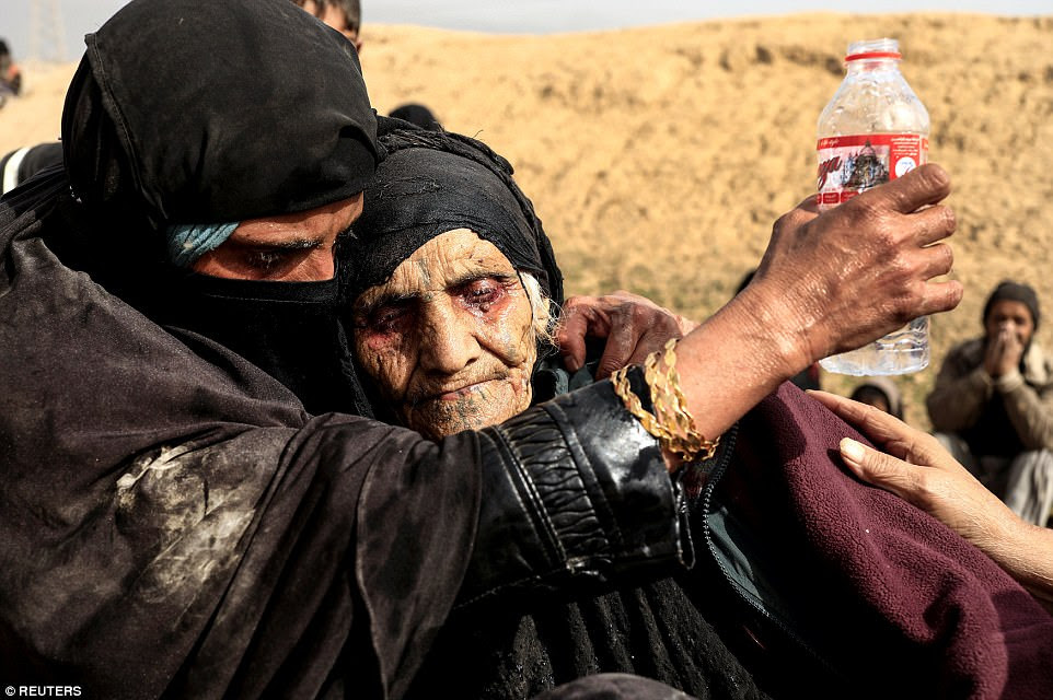 Displaced Iraqi women rest in the desert after fleeing their homes. They await transportation as the country's army battles with Islamic State jihadists in western Mosul on February 27