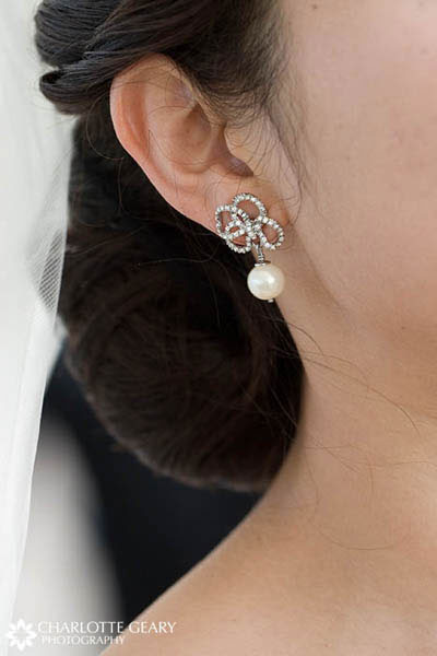 Bride with chignon and white flower in her hair Diamond and pearl earrings
