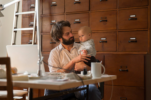 Young designer with baby son in home office : Stock Photo