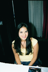 A black-haired woman wearing a yellow top and jeans sitting behind a table looking up at the camera.