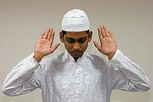 English: A Muslim raises his hands in Takbir, ...