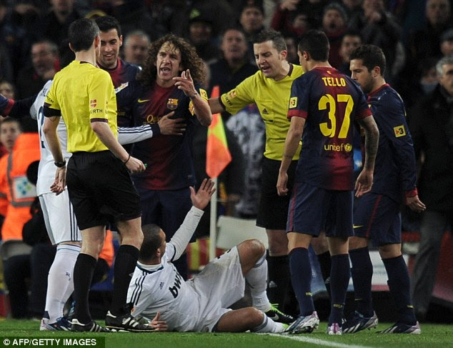 Heated: Pepe fell to the floor as tensions ran high between the arch rivals