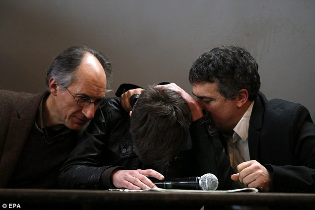 Emotional: The new editor-in-chief of French satirical newspaper Charlie Hebdo, Gerard Biard (left), and Journalist Patrick Pelloux (right) comfort cartoonist Luz (centre) during a press conference at which they vowed to go on with their work and confirmed details of tomorrow's edition after last week's massacre