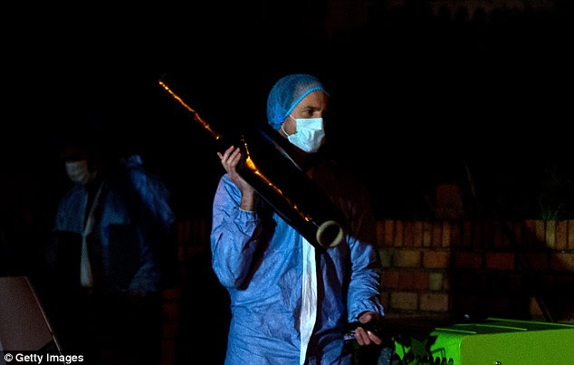 Prepared: A forensic worker carries plastic sheeting into the property as they continue to gather evidence