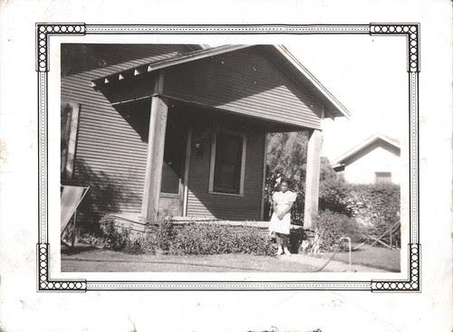 Girl in white dress in front yard