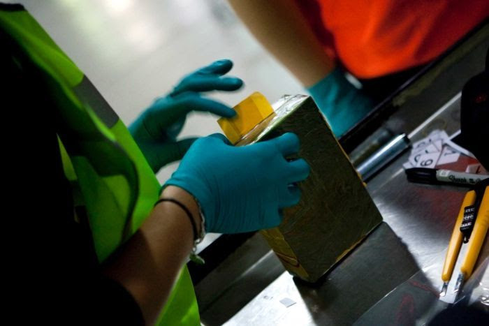 Customs officers examine a package of heroin.