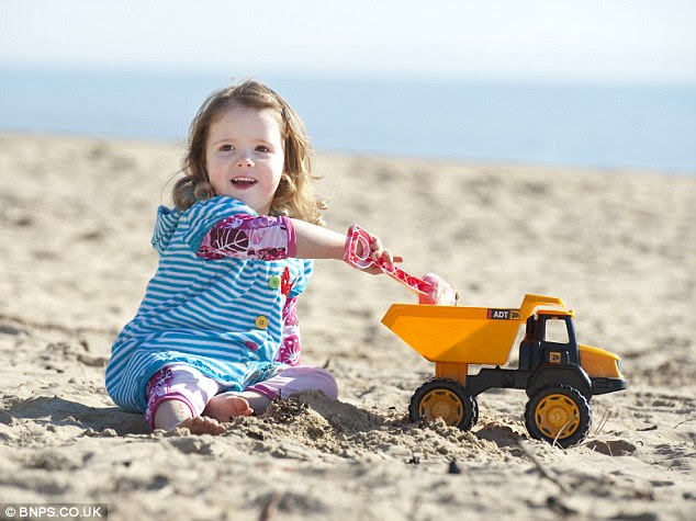 'Beach weather': Masie Kennedy, aged two, plays on the sand on the beach at Bournemouth today