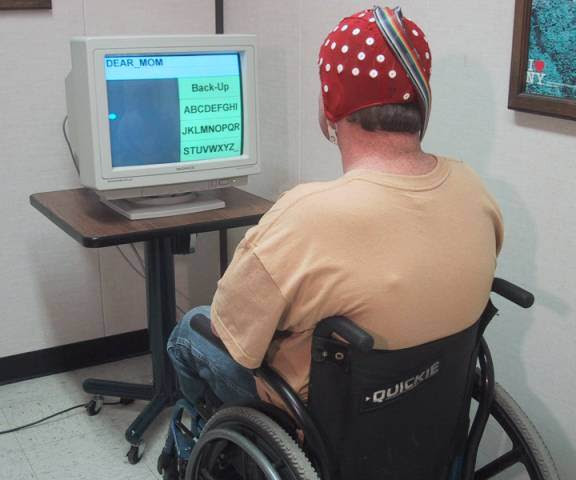 Photo of a man in a wheelchair sitting at a computer with a red cap with EEG nodes