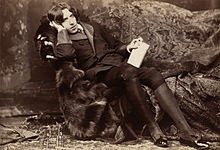A tall man rests on a chaise longue, facing the camera. On his knees, which are held together, he holds a slim, richly bound book. He wears knee breeches which feature prominently in the photograph's foreground.