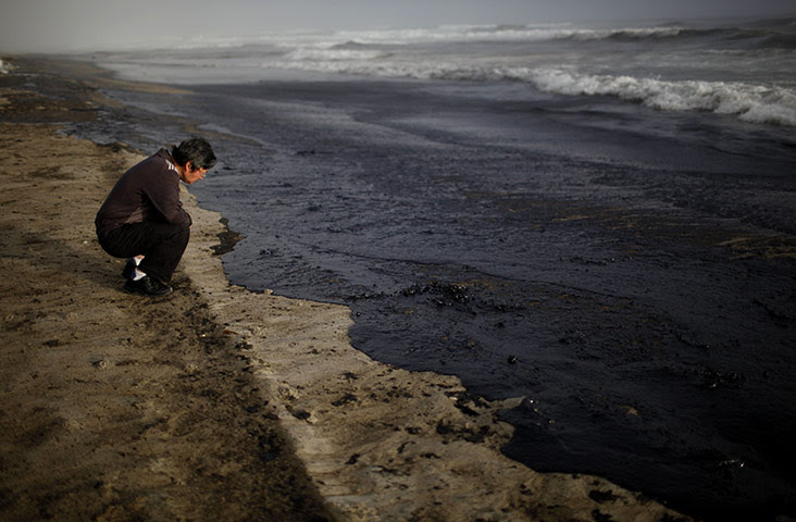 Ρένα oild διαρροή: Ένας άνδρας βλέπει τα κύματα που έρχονται στην παραλία Papamoa, Tauranga, Νέα Ζηλανδία