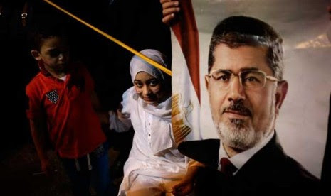 Seorang anak membawa poster Presiden Muhammad Mursi di kawasan masjid Rabaah al-Adawiya di Nasr City, Kairo,   Rabu (31/7).