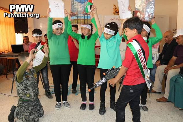In a sick classroom play children at the Al-Surra School surround a classmate dressed as an Israeli soldier to play out a mock 'execution'