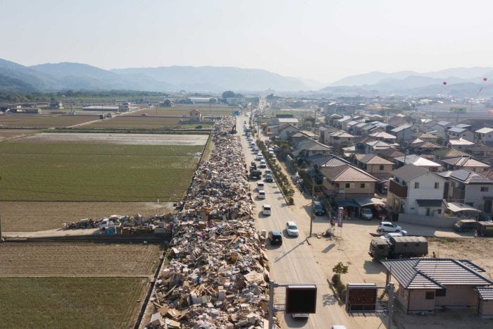 An aerial shot shows rubbish piled up alongside a road for as far as the eye can see.