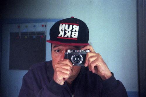 reflected self-portrait with Halina 35X camera and RUN BKK baseball cap by pho-Tony