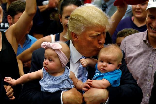 Republican presidential nominee Donald Trump kisses a baby at a campaign rally in Colorado Springs, Colorado, U.S., July 29, 2016. REUTERS/Carlo Allegri