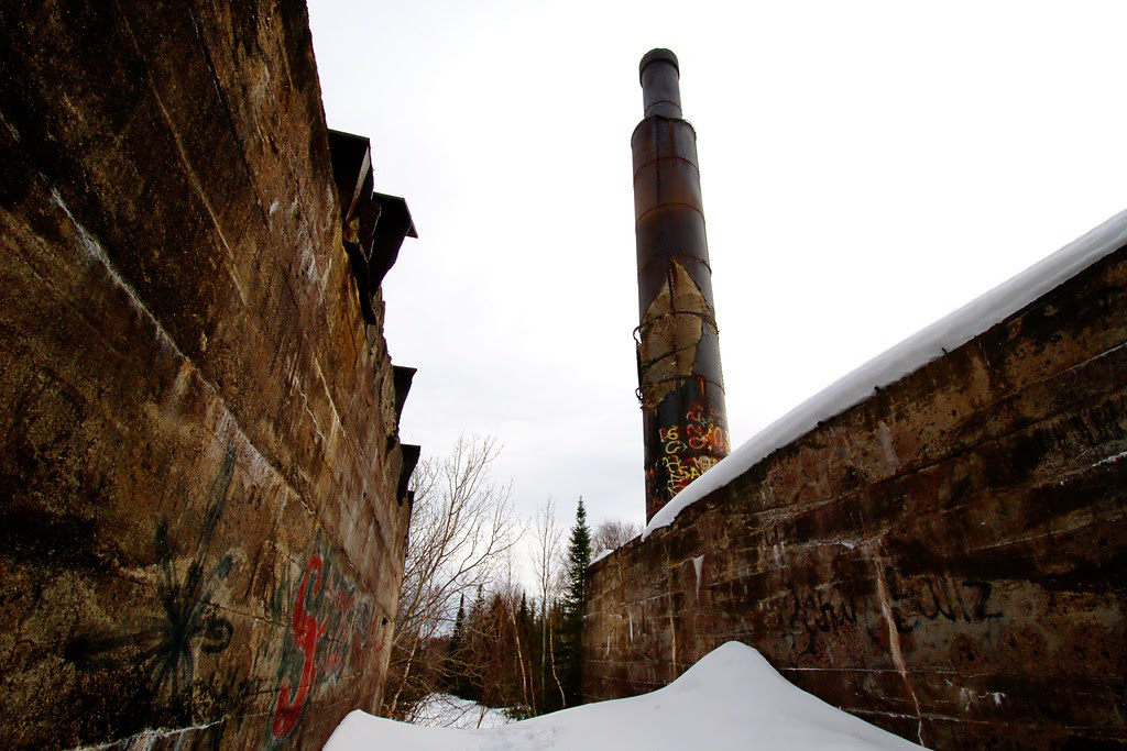 A worn cement rockhouse foundation with a large metal tower in the background.